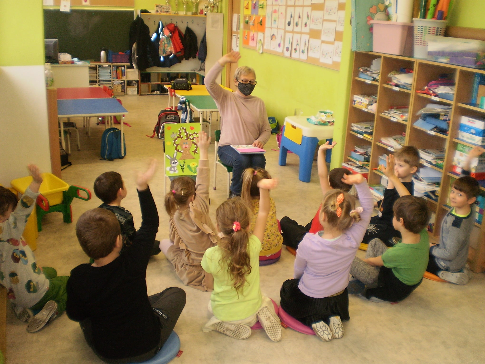 Nauczyciel siedzi na krześle, obok na sztaludze plakat wiosenny, dzieci siedzą na dywanie i zgłaszają się do odpowiedzi