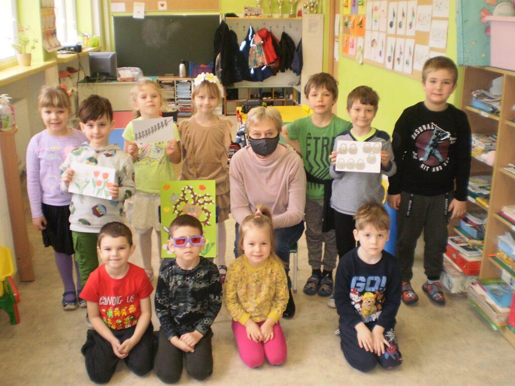 zdjęcie grupowe: 7 dzieci stoi, 4 dzieci siedzi, pośrodku między nimi siedzi nauczyciel.