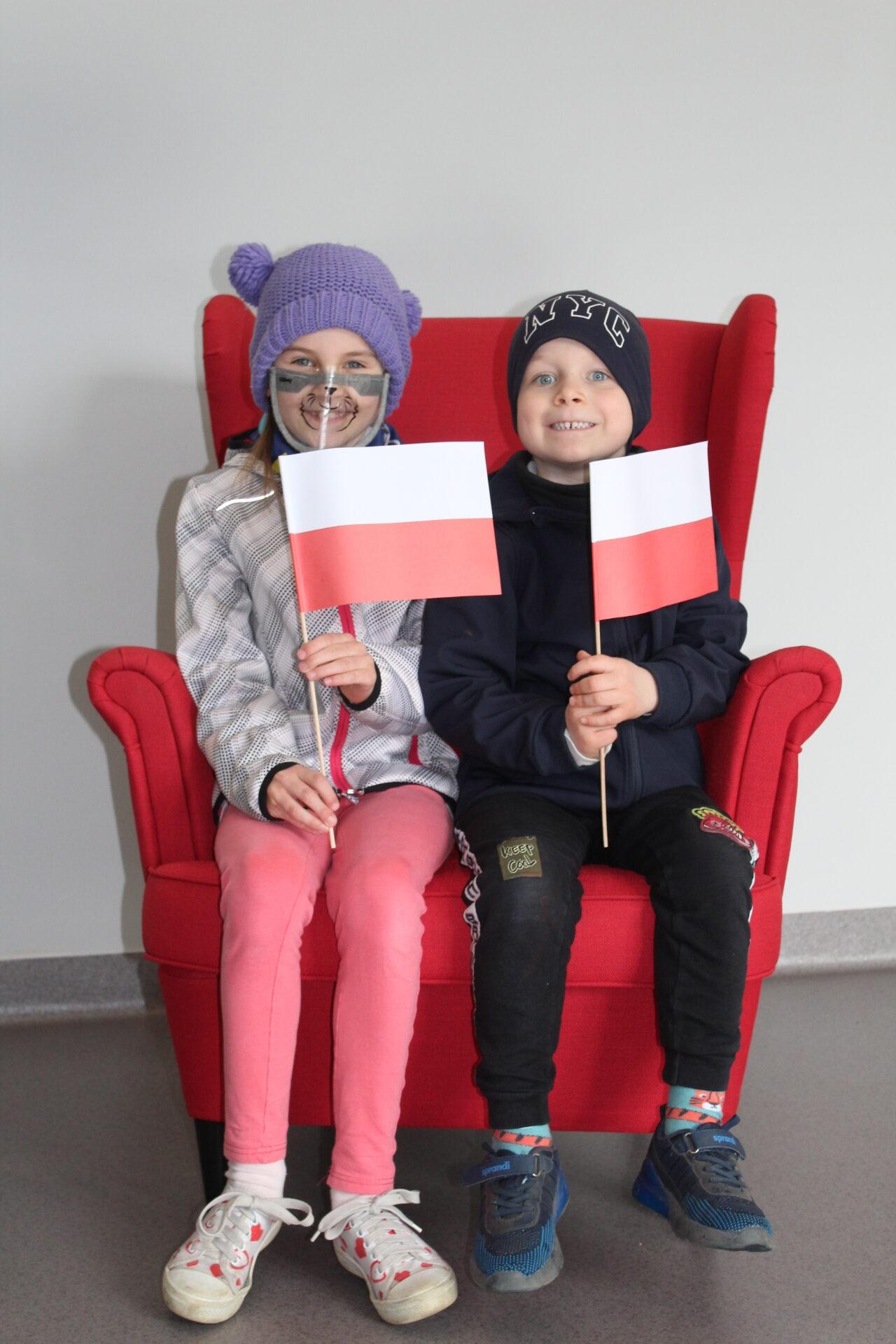 dzieci z flagami polskimi na fotelu