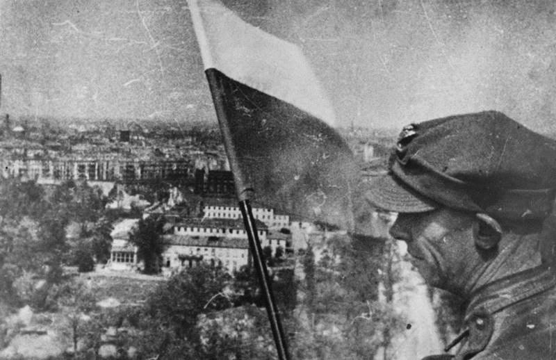 polski żołnierz stawia biało-czerwona flagę wBerlinie