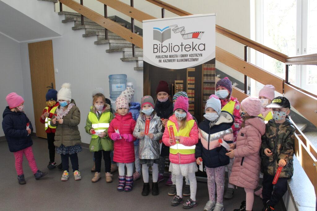 dzieci stoją przy banerze biblioteki  zzakłądkami doksiążek