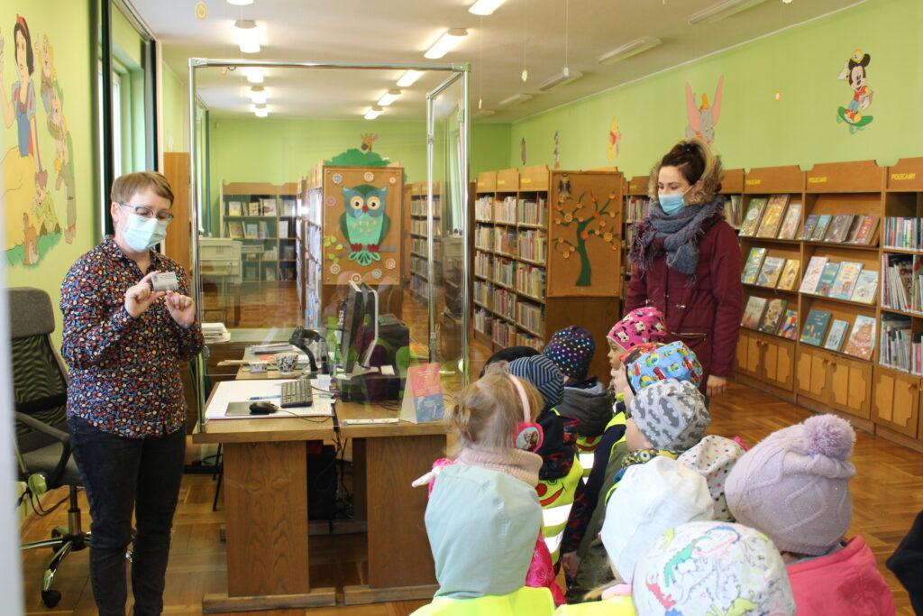 bibliotekarz pokazuje dzieciom kartę biblioteczną