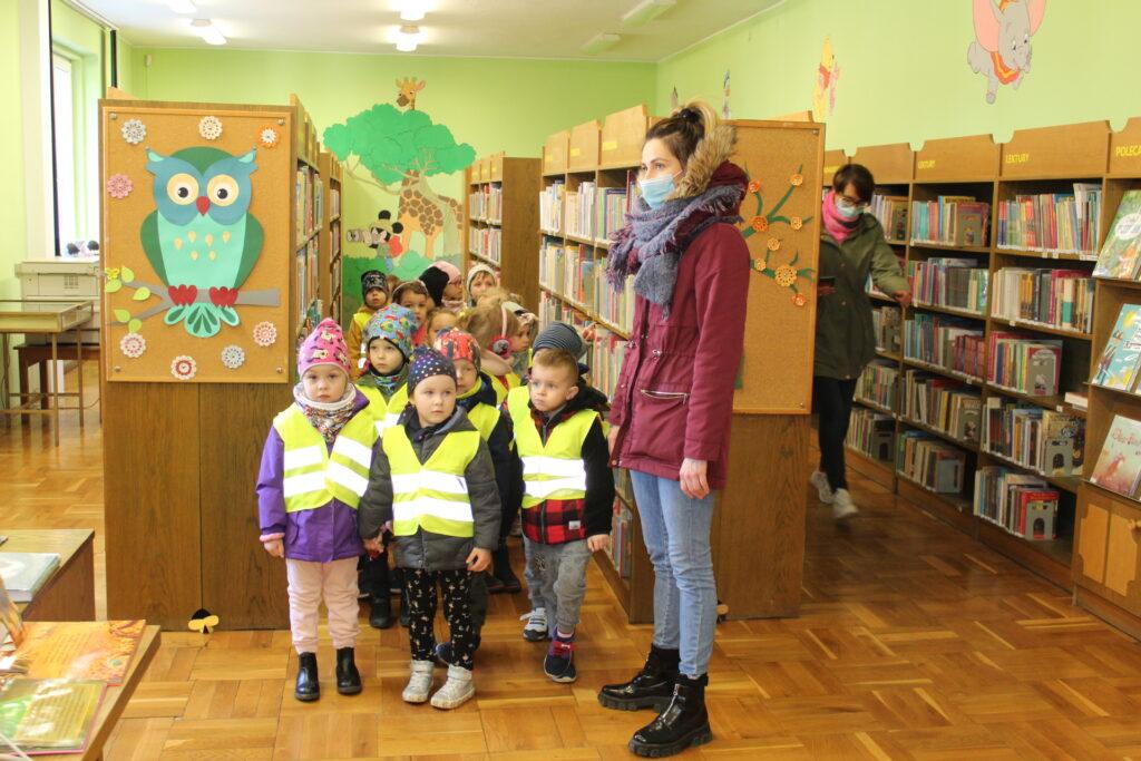 Grupa dzieci stoi między regałami zksiązkami