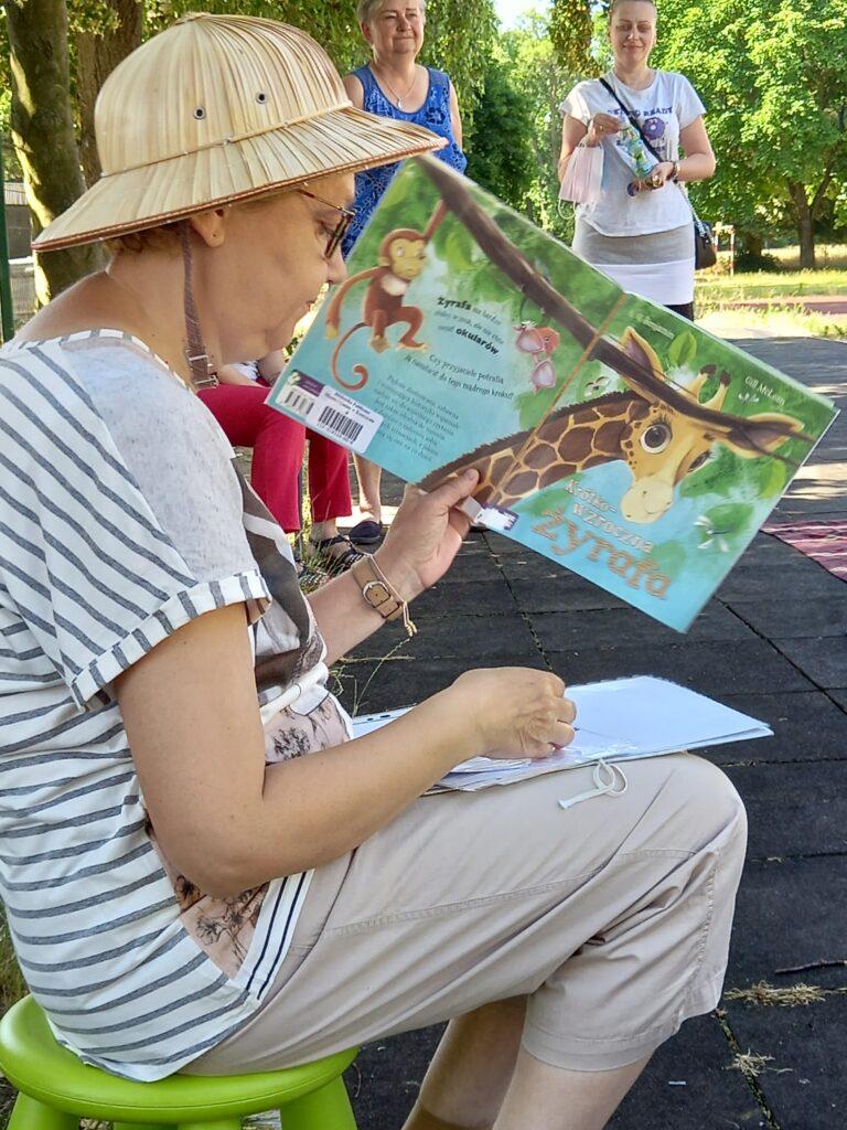 Bibliotekarka wcieniu drzewa czyta dzieciom książkę ożyrafie.