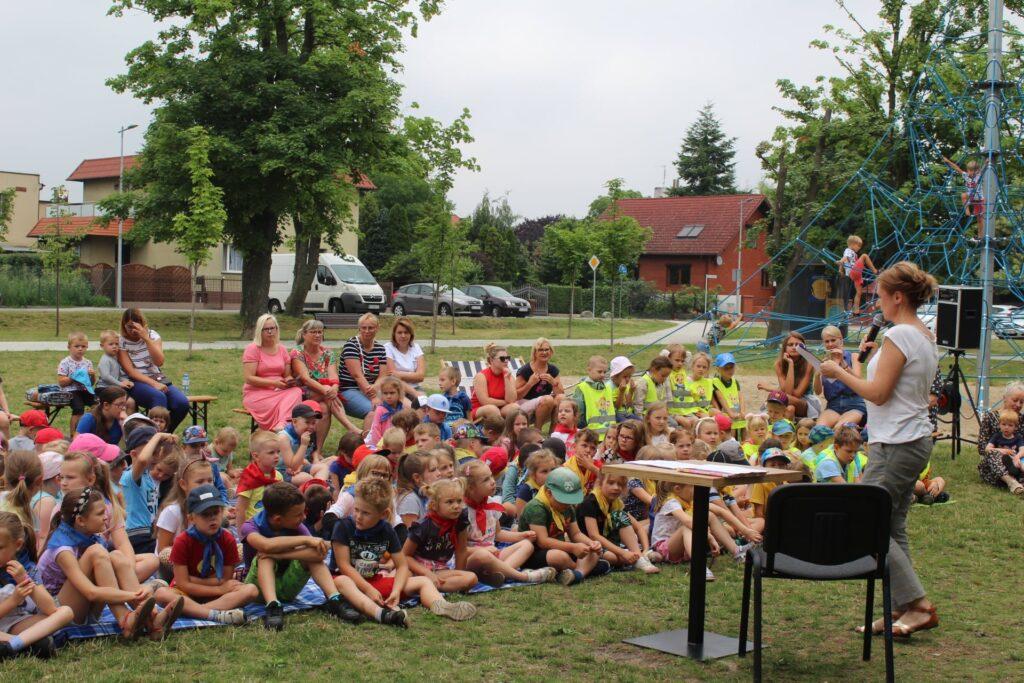 W Parku Miejskim Dzieci siedzące natrawie rozwiązują zagadki.