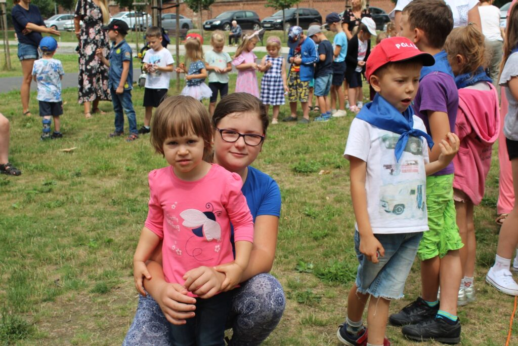 Dwie dziewczynki natle pozostałej grupy dzieci.