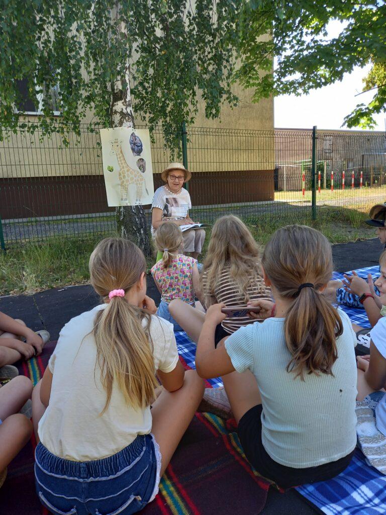 Bibliotekarka zgrupą dzieci podczas czytania naLiterackim Przedpołudniu.