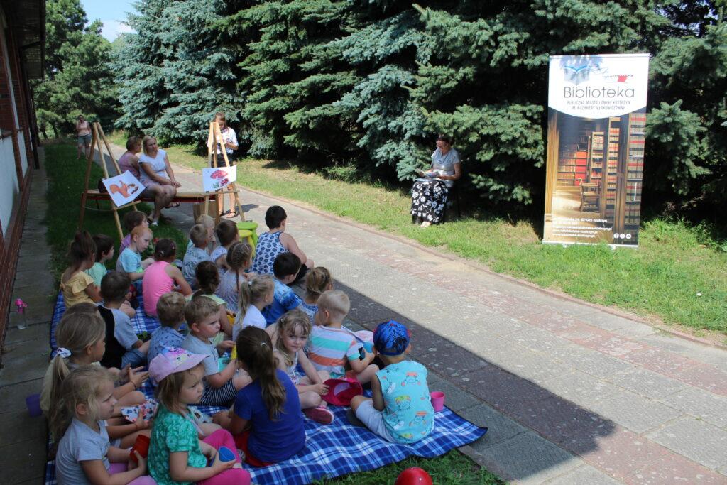 Bibliotekarka czyta wplenerze grupie dzieci