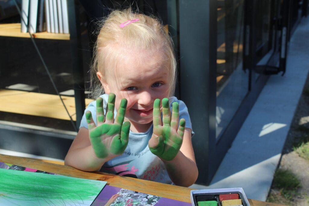 Mała uczestniczka pleneru pokazuje pomalowane nazielono dłonie