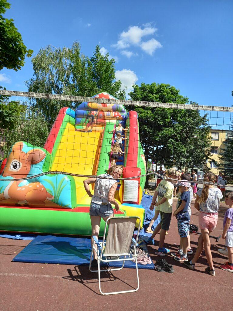 Grupa dzieci bawi się wzjeżdżanie zdmuchanego zamku.