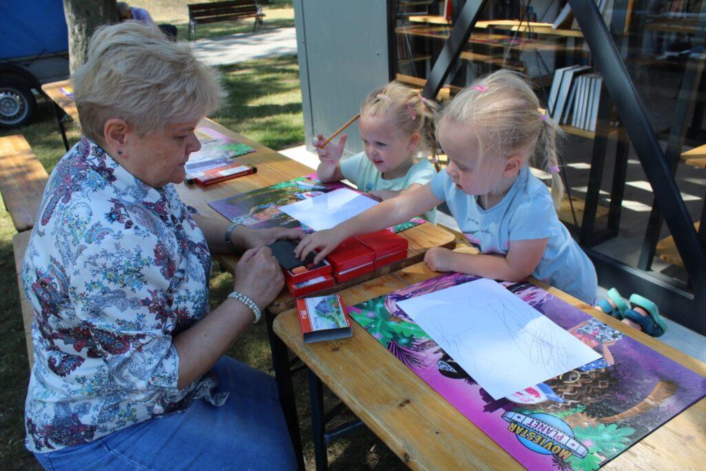Najmłodsze uczestniczki pleneu rysunkowego wraz zpanią prowadzącą zajęcia