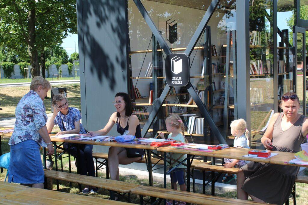 Przy Stacji Książki siedzą uczestnicy pleneru rysukowego