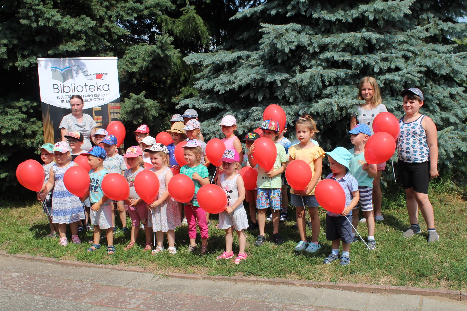 Grupa przedszkolaków z Czerlejna z czerwonymi balonikami w tle rollup biblioteki w Kostrzynie