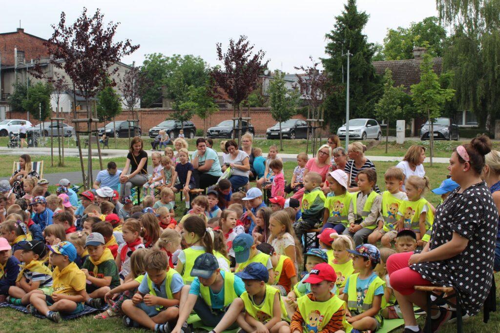 Grupa dzieci wraz zopiekunami podczas czytania bajki.