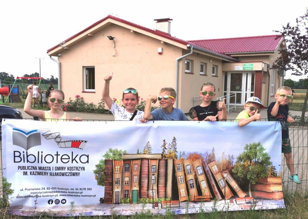 Uczestnicy spektaklu natle baneru biblioteki