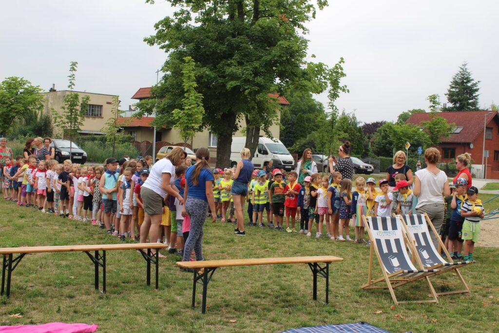 Dzieci podzielone nadrużyny bawią się wszybkie podawanie sobie piłki.