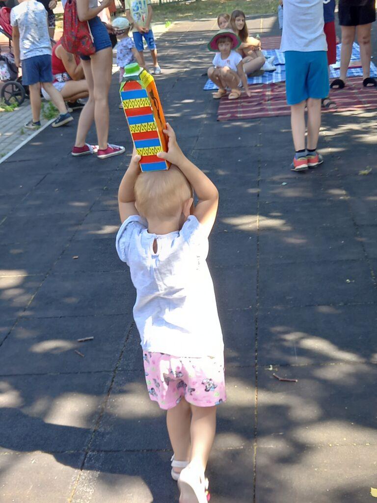 Małe dziecko próbuje utrzymać kartonik nagłowie.