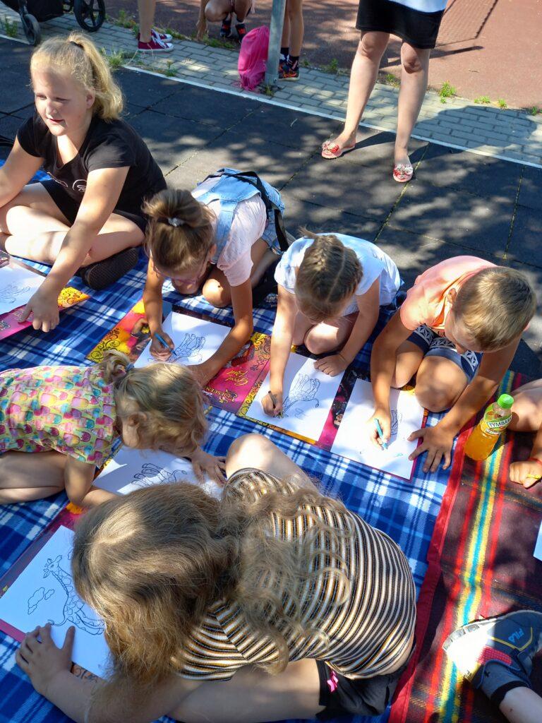 Grupa dzieci zajęta rysowaniem nakocu rozłożonym poddrzewem.