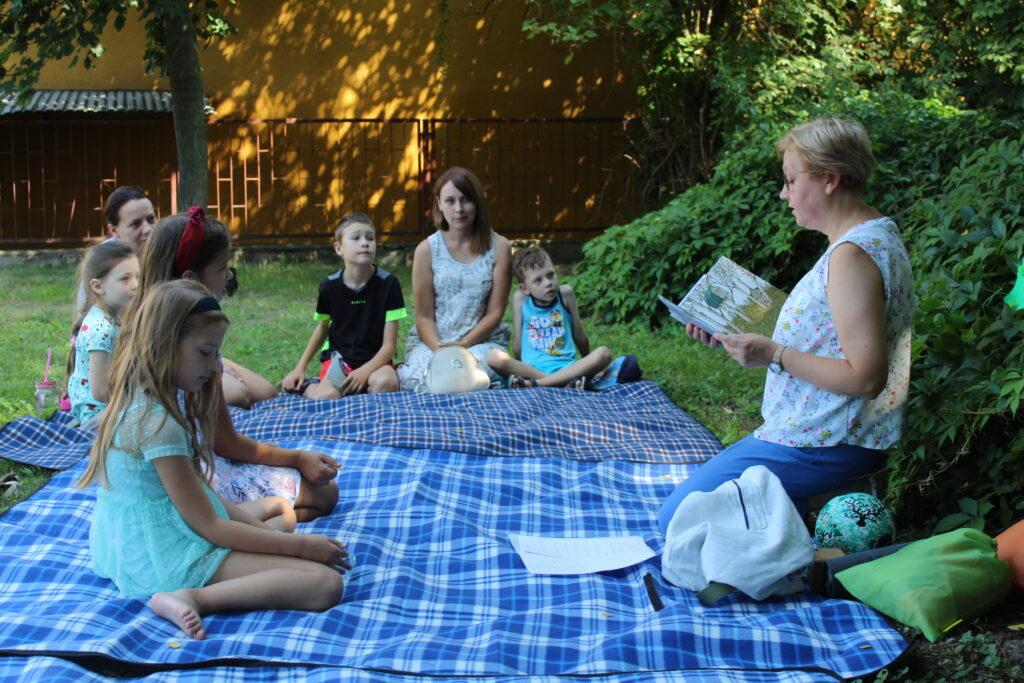 Na kocach rozłożonych natrawie siedzą dzieci zopiekunkami isłuchają opowiadania czytanego przezbibliotekarkę.