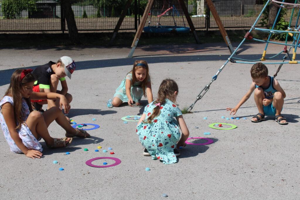 """Na placu zabaw przy szkole wGułtowach kilkoro dzieci bawi się w""""pchełki""""."""