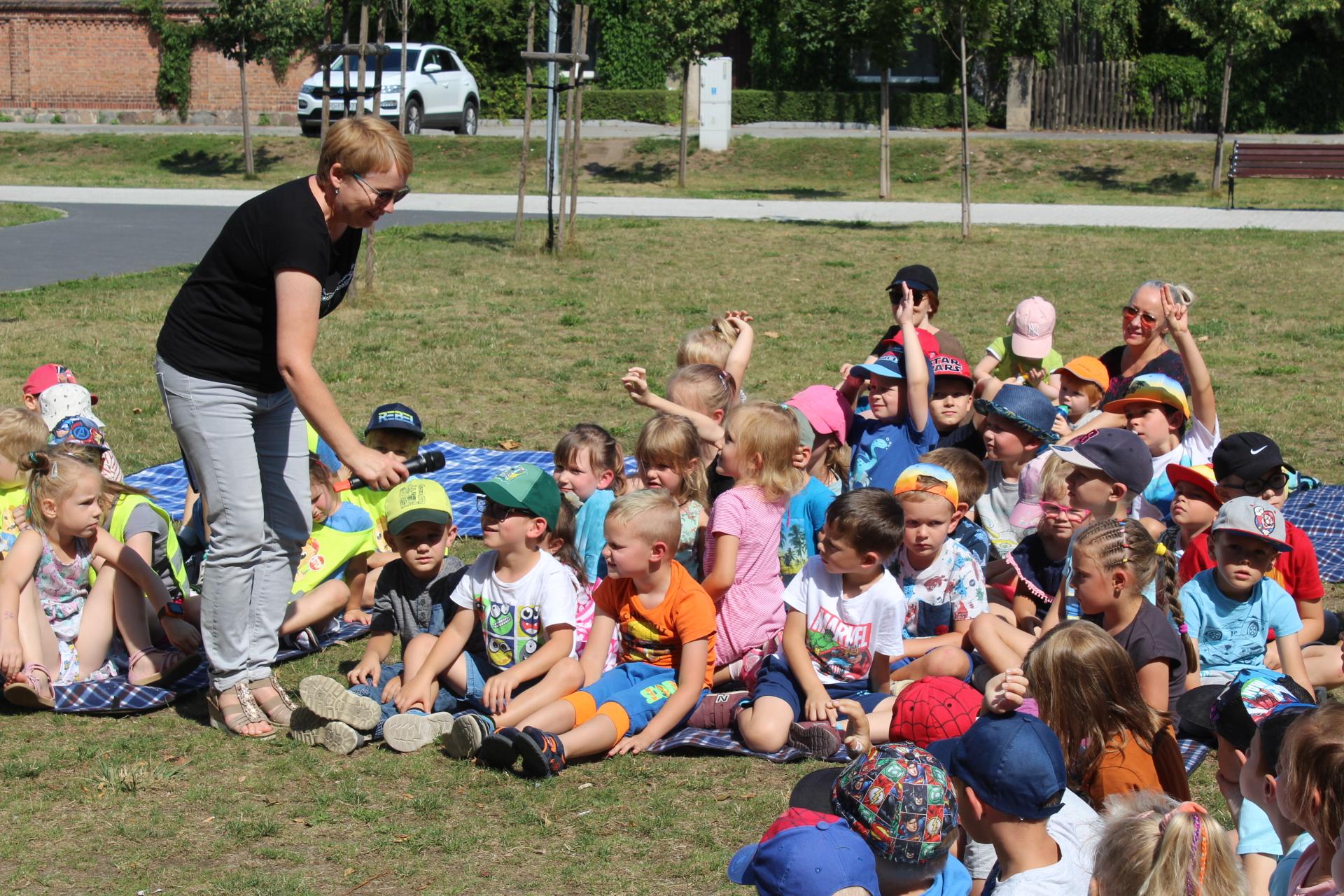 Bibliotekarka zadaje zgromadzonym w Parku Miejskim dzieciom pytania.