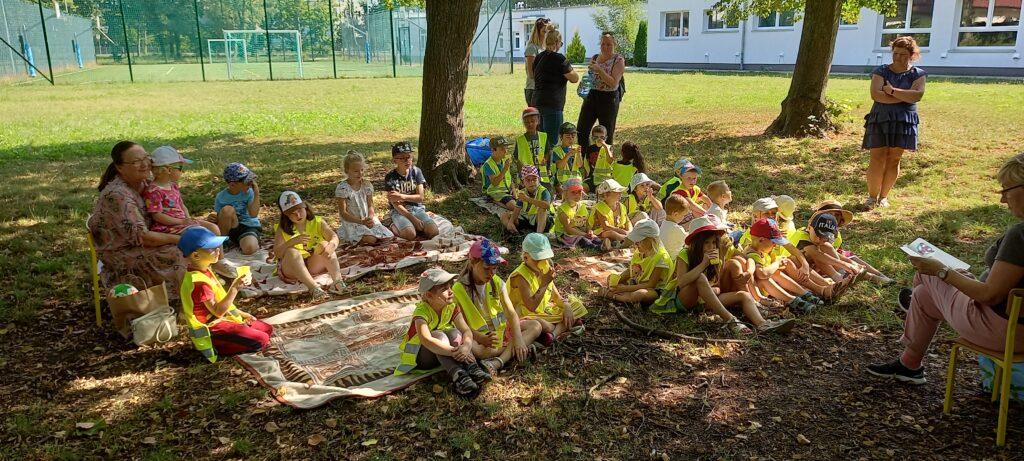 Na trawie, wcieniu drzew, grupa dzieci słucha czytającej bibliotekarki.
