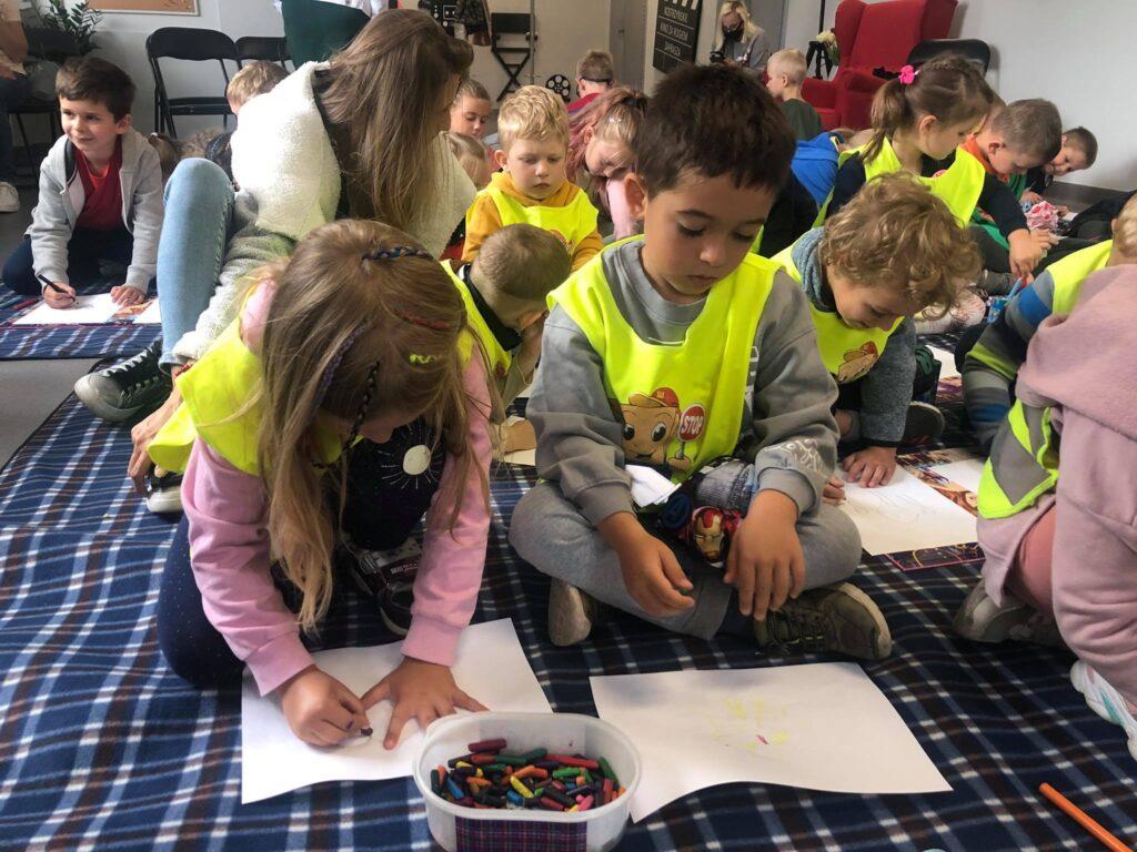 Grupa dzieci naholu biblioteki wykonuje swoje rysunki.