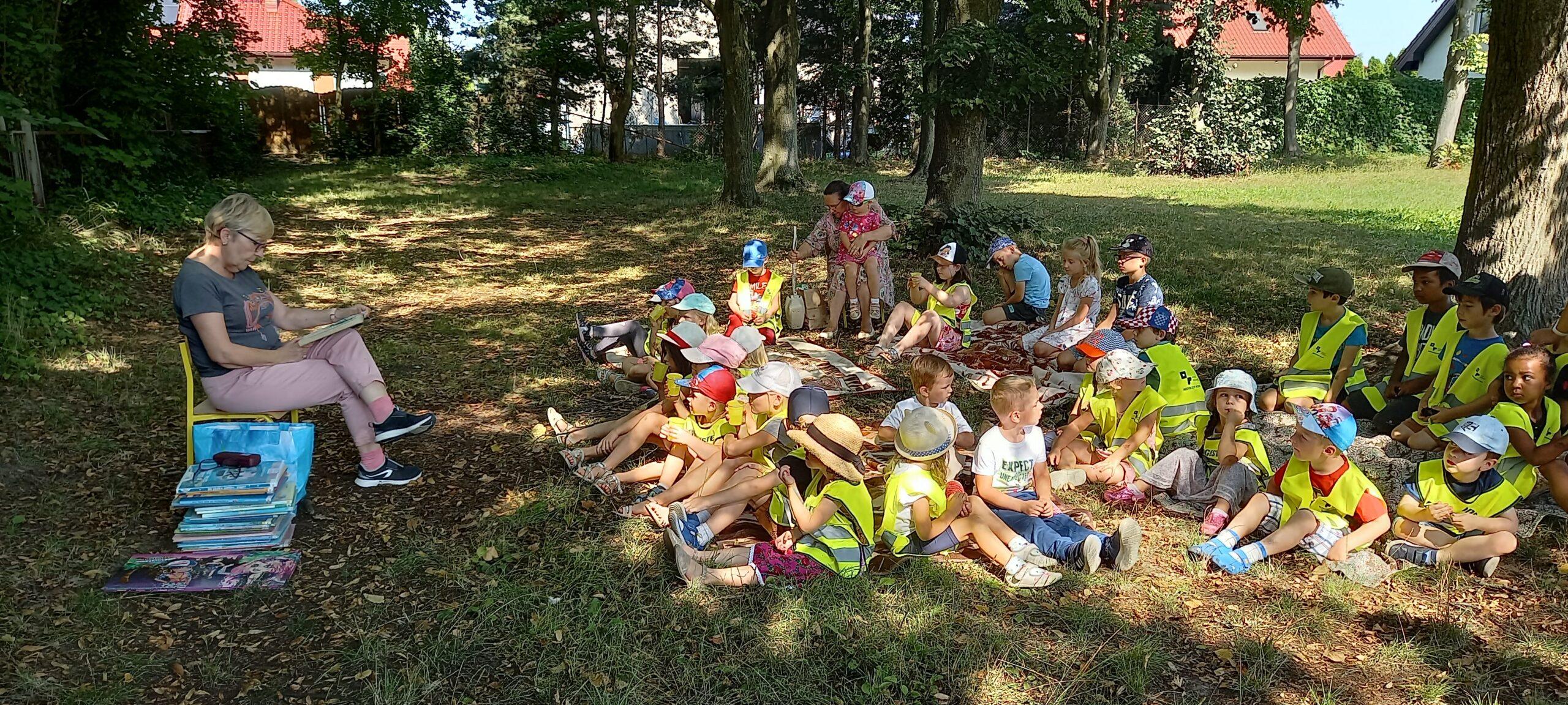 Po lewej stronie bibliotekarka czytająca wiersze, po prawej - grupa dzieci wraz z opiekunami siedzi na trawie.