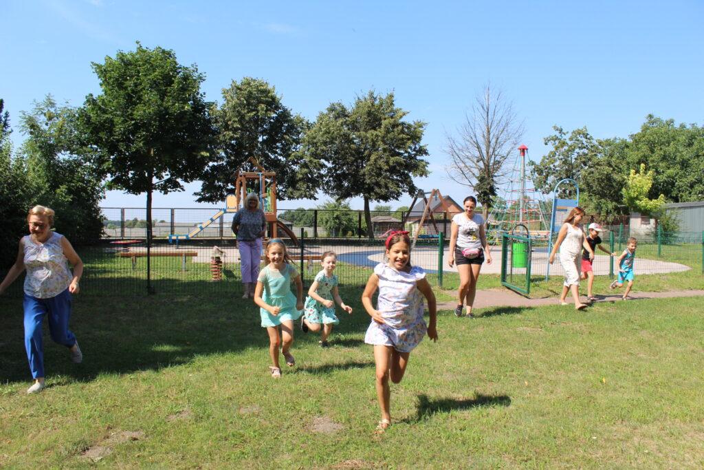 Grupa uczestników Literackiego Przedpołudnia biegnie odstrony placu zabaw.