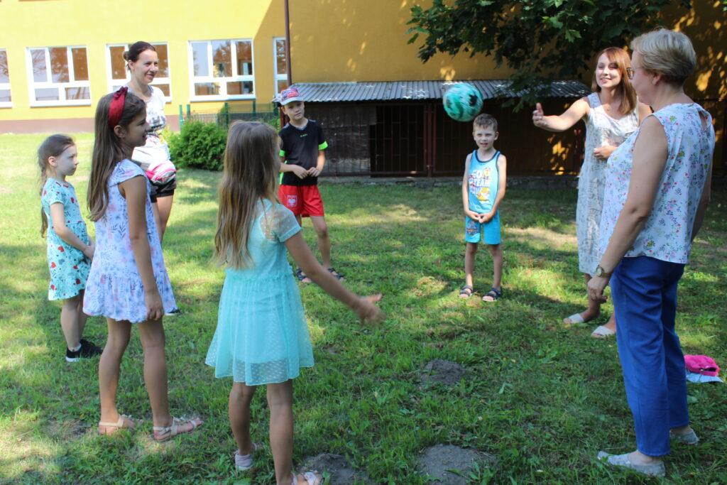 Uczestnicy spotkania stoją wkręgu ipodają sobie piłkę.