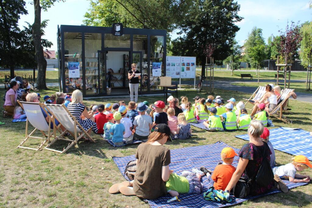 W Parku Miejskim przy Stacji Książki bibliotekarka zadaje dzieciom zagadki.
