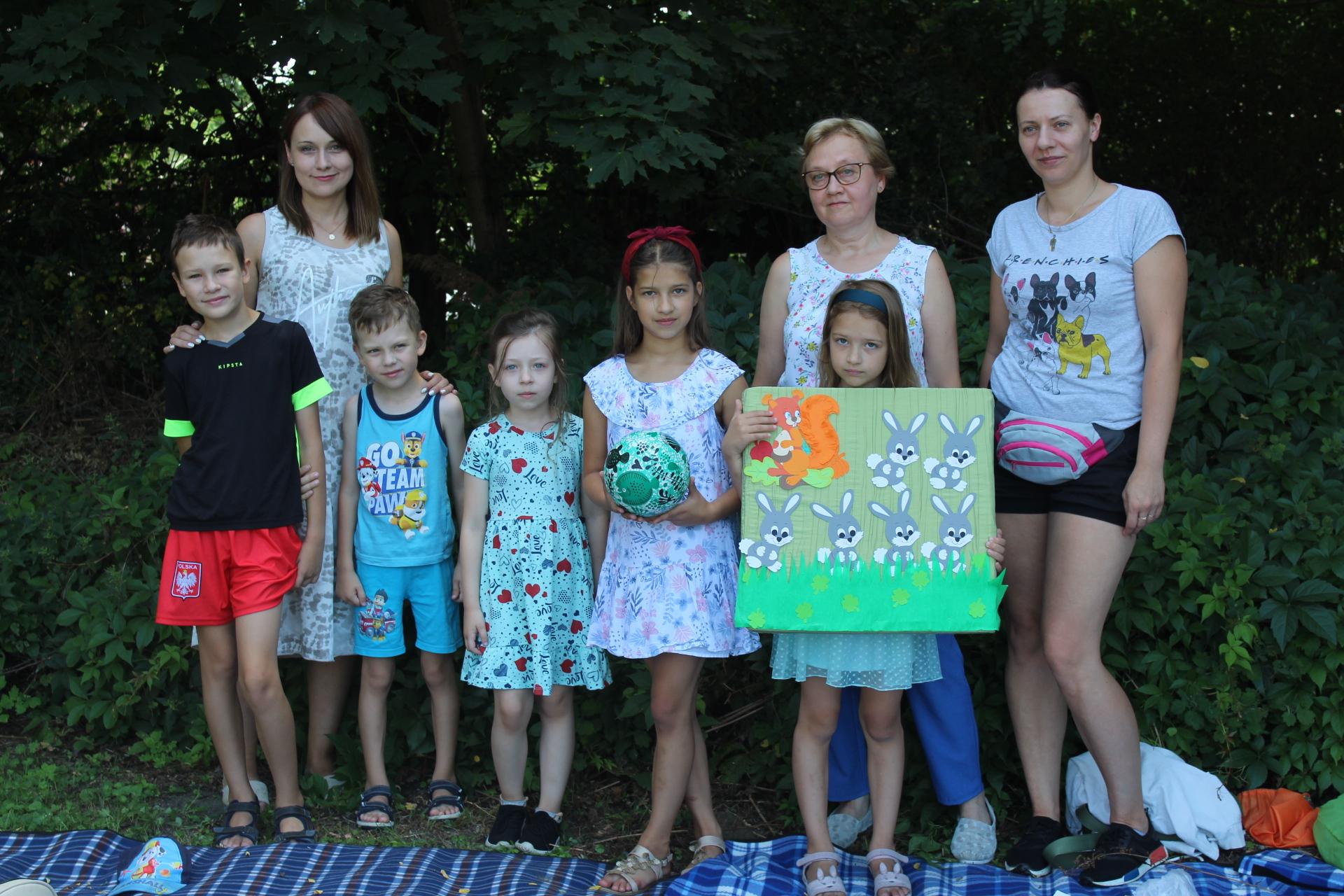 Uczestnicy Literackiego Przedpołudnia pozują do wspólnego zdjęcia na tle zieleni.