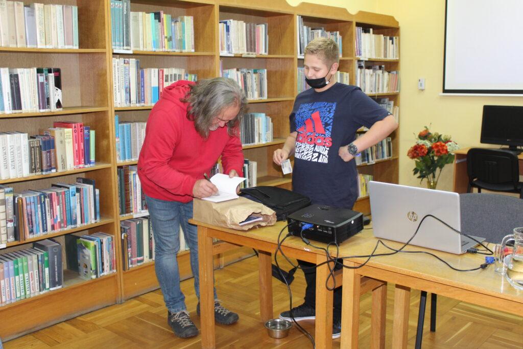 Krzysztof Nowakowski składa autograf wswej książce.