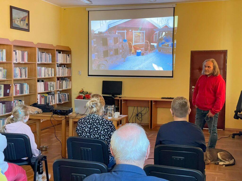W czytelni biblioteki grupa ludzi słucha opowiadającego owyprawach Krzysztofa Nowakowskiego.