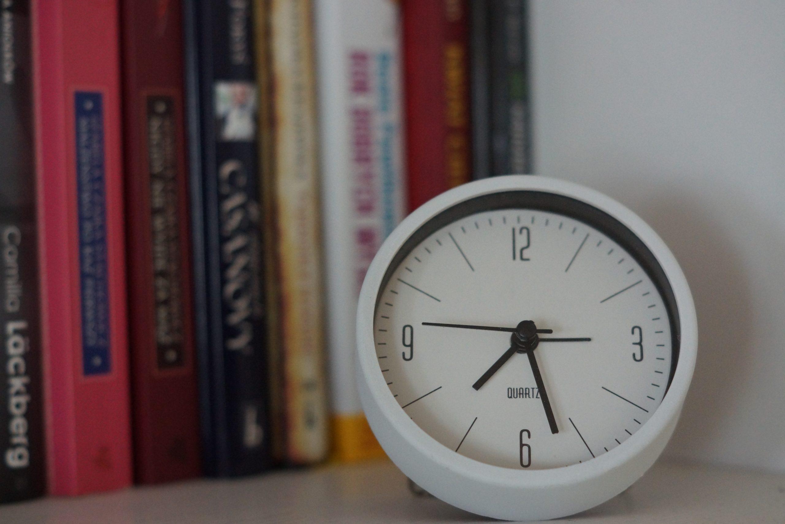 biały zegar, w tle książki